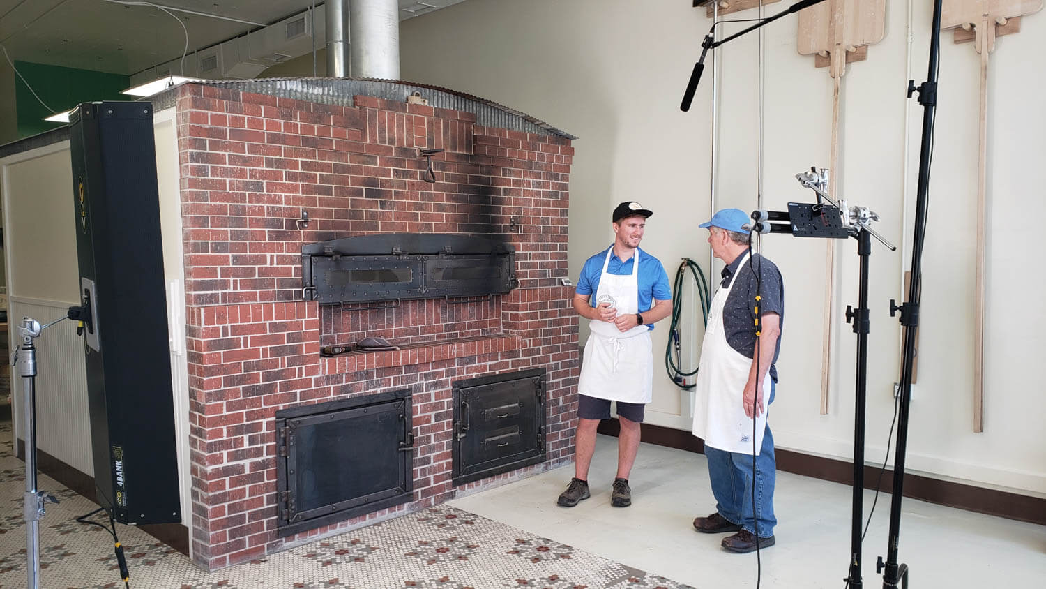 2 people standing in front of a giant brick oven