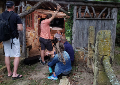 people filming an interview in an old wooden cottage